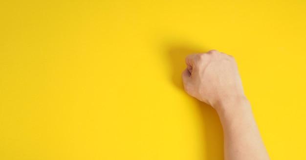 Ręka pięści na żółtym tle. prawa ręka człowieka.
