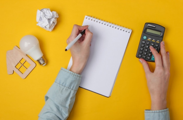 Ręka pisać w notesie i używać kalkulatora na żółto
