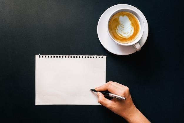 Ręka pisząca na białym papierze z filiżanką kawy latte na drewnianym biurku, widok z góry