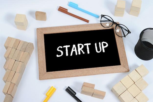 Ręka pisząca startup na tablicy