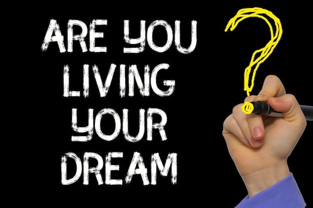 Ręka pisząca tekst: czy żyjesz swoim marzeniem?
