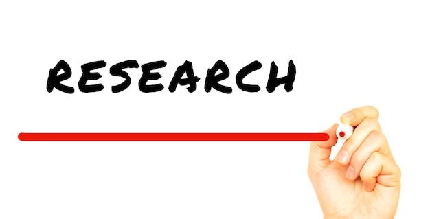 Ręka pisze badania z czerwonym markerem. na białym tle pomysł na biznes.
