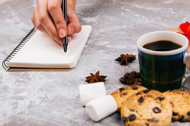 Ręka pisze coś w notatniku przed filiżanką kawy i wyśmienicie ciastkami