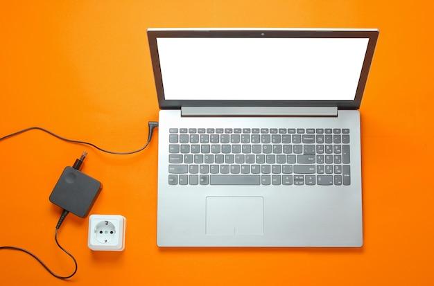 Ręka podłącza ładowarkę do laptopa do gniazdka elektrycznego na pomarańczowym tle