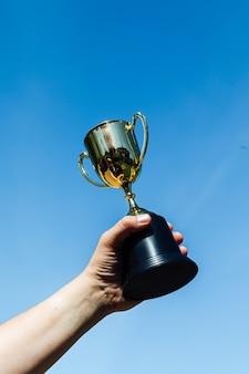 Ręka podnieś kieliszek mistrza z niebem w tle. koncepcja zwycięstwa