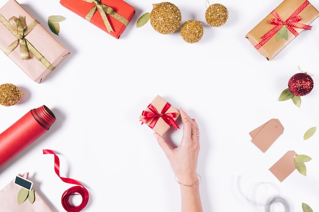 Ręka podnosi małe pudełko z prezentem