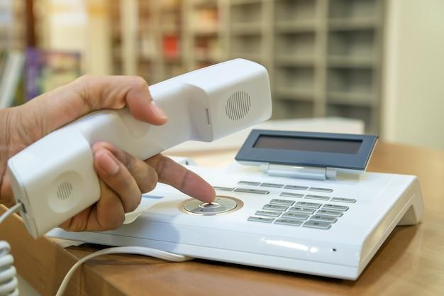 Ręka podnosi słuchawkę i naciska przycisk na telefonie biurowym lub starym telefonie.