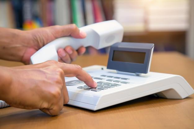 Ręka podnosi słuchawkę i naciska przycisk na telefonie biurowym.
