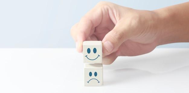Ręka podnosząca klocki z uśmiechniętą i smutną twarzą na białej powierzchni