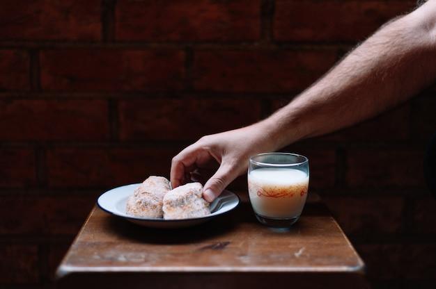 Ręka podnosząca słodycze ze stołu i szklankę mleka obok talerza
