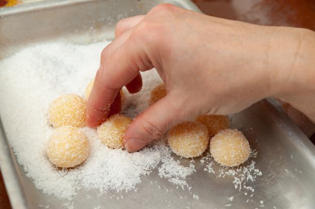 Ręka podnosząca tradycyjne brazylijskie słodycze o nazwie beijinho de coco w brazylijskim portugalskim