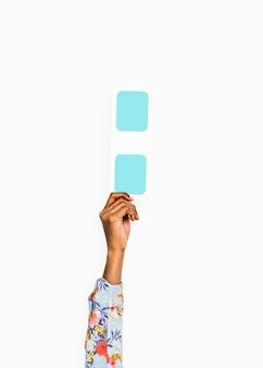 Ręka podnoszona trzymając niebieski dwukropek