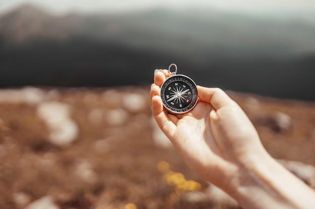Ręka podróżnika trzyma kompas na pięknych karpatach