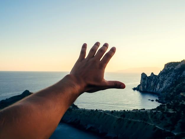 Ręka podróżnika turystycznego człowieka na tle morza i nieba
