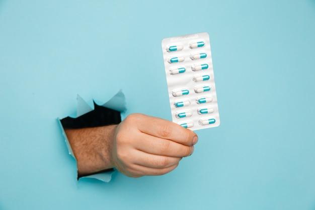 Ręka pokazująca blister tabletek z dziury rozdartej w niebieskiej ścianie papieru. reklama opieki zdrowotnej, farmaceutyków i leków
