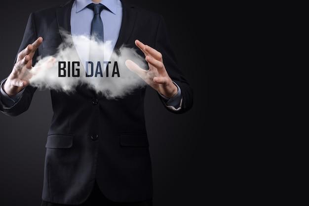 Ręka pokazująca chmurę słowami big data na ciemnym tle.