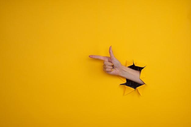 Ręka pokazuje gest dwoma palcami przez rozdarty żółty papier tle.