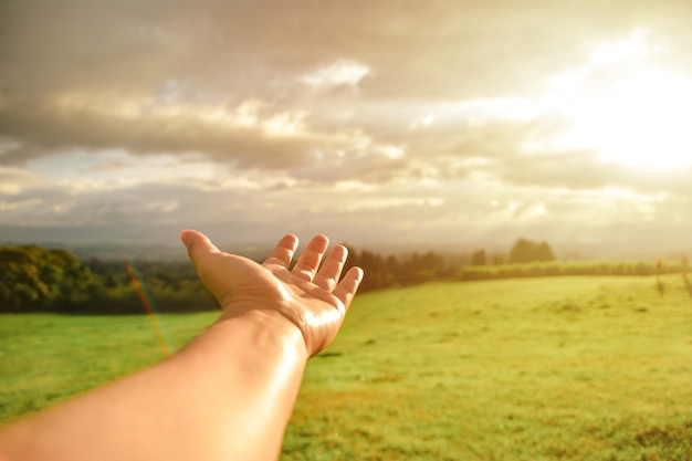 Ręka pokazuje krajobraz sunset grass sky rainbow