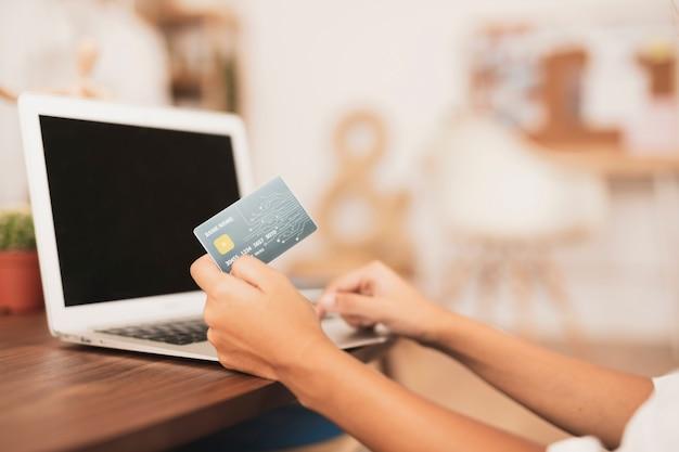 Ręka pokazuje kredytową kartę próbną up z zamazanym tłem