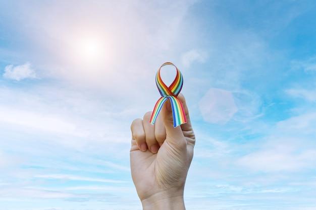 Ręka pokazuje lgbtq rainbow wstążki na tle nieba w godzinach porannych.