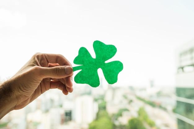 Ręka pokazuje zielonego papieru shamrock i widok pejzaż miejski