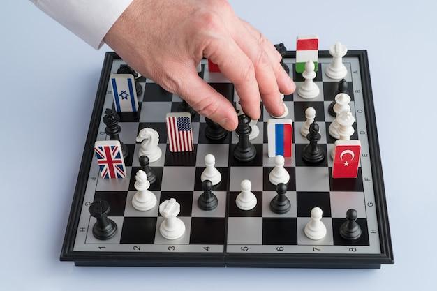 Ręka polityka porusza figurą szachową. koncepcyjne zdjęcie gry politycznej i strategii.