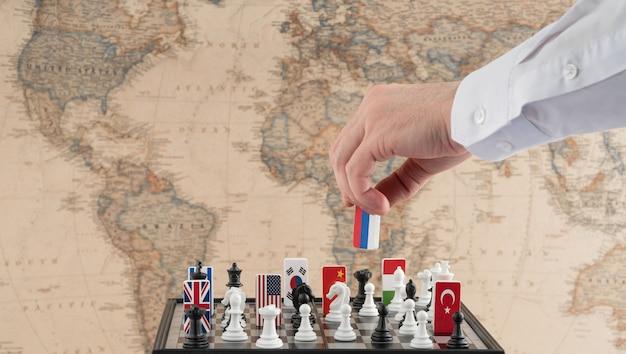 Ręka polityków przesuwa figurę szachową z flagą koncepcyjne zdjęcie partii politycznej