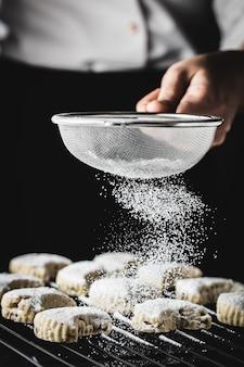 Ręka posypująca cukrem pudrem smaczne tradycyjne ciasteczka kawala