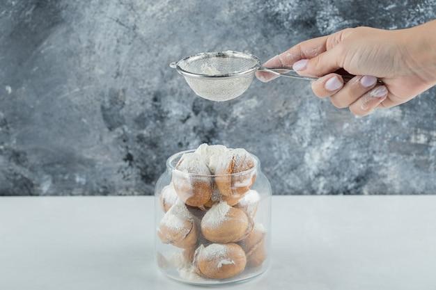 Ręka posypywanie cukru pudru na ciasteczka w kształcie orzecha włoskiego.