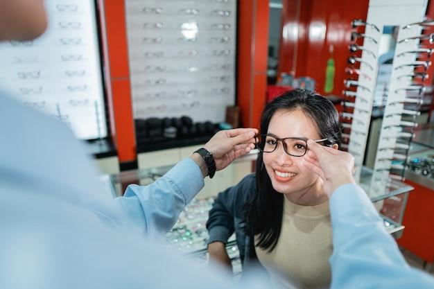 Ręka pracownika pomaga założyć okulary, które kobieta, która przeprowadzała badanie wzroku, wybrała w klinice okulistycznej