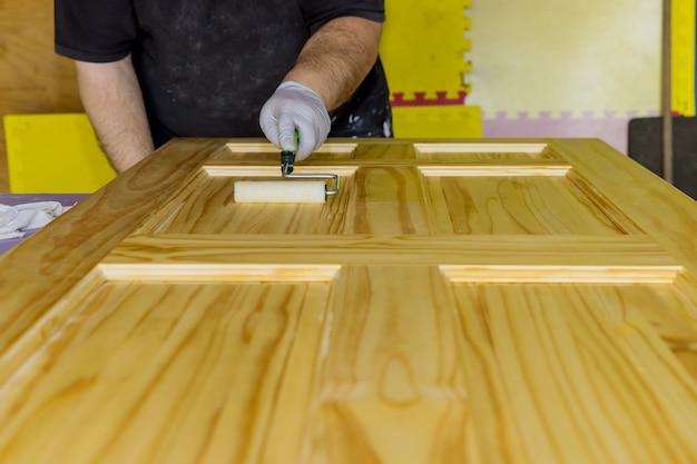 Ręka pracownika trzyma pędzel malujący nowe drewniane drzwi wejściowe za pomocą wałka ręcznego