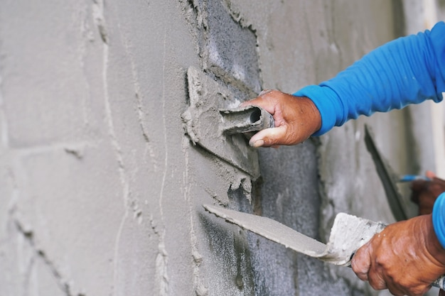 Ręka pracownika tynkarski cement na ścianie