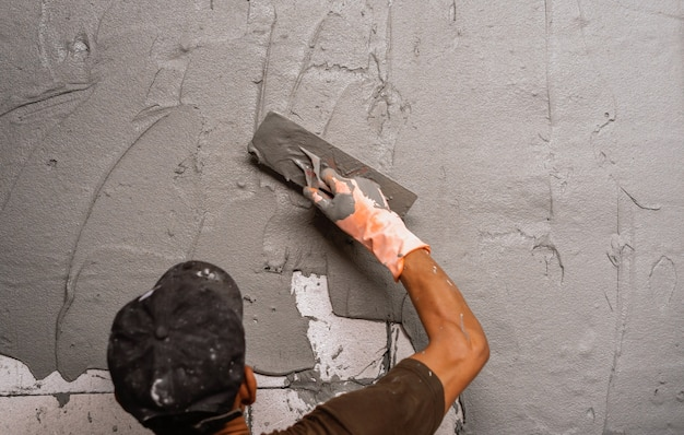 Ręka pracownika tynkującego cement na ścianie do budowy domu na placu budowy