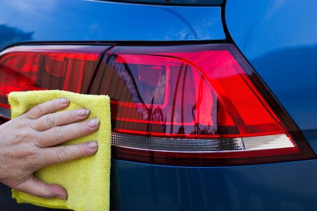 Ręka pracownika używa czystej żółtej szmatki do wycierania samochodu po umyciu w myjni.