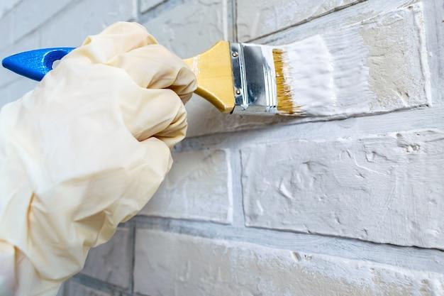 Ręka pracownika w lekkich gumowych rękawiczkach maluje drewnianą szczotką ścianę z cegły białą farbą, koncepcja naprawy. renowacja wnętrz.