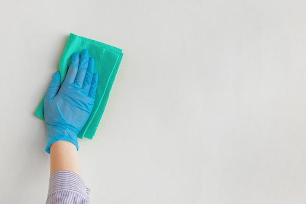 Ręka pracownika w niebieskiej gumowej rękawicy do wycierania ściany z kurzu suchą szmatką.