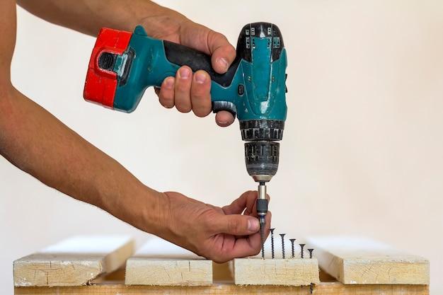 Ręka pracownika wkręca wkręt w drewnianą deskę za pomocą wkrętarki akumulatorowej. mężczyzna cieśla przy ręcznie robioną pracą