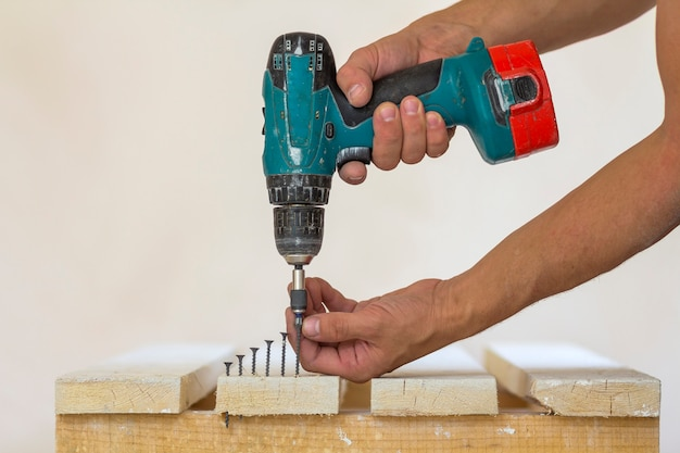 Ręka pracownika wkręca wkręt w drewnianą deskę za pomocą wkrętarki akumulatorowej