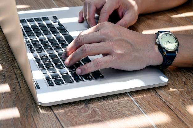 Ręka pracuje na laptopie pod światłem i cieniem mężczyzna.