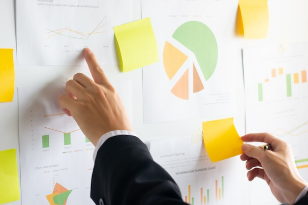 Ręka pracuje pieniężne dane i analizuje na wykresie biznes