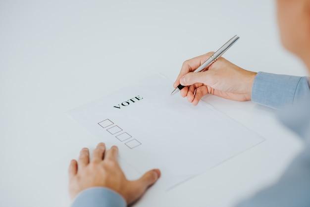 Ręka próbuje głosować w papierze