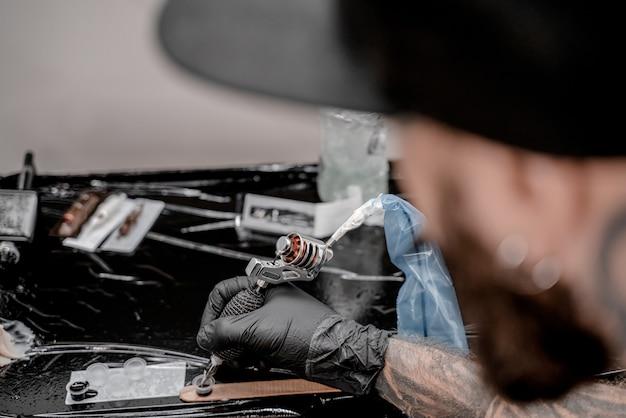 Ręka profesjonalnego artysty z maszynką do tatuażu, wazeliny i plastikowych kubków z atramentami, widok z bliska.