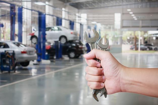 Ręka profesjonalnego mechanika samochodowego z kluczem