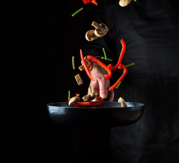 Ręka profesjonalnego szefa kuchni rzuca kawałki warzyw i grzybów na patelnię na czarnym tle. koncepcja gotowania restauracji. bezpłatna powierzchnia reklamowa