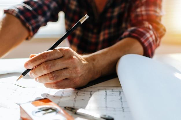 Ręka profesjonalny architekt, inżynier lub wnętrze ręce rysunek z plan na biurku w miejscu pracy