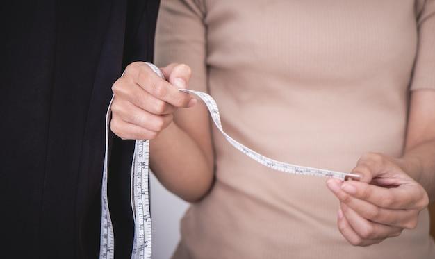 Ręka projektant mody mierzy ubrania z taśmy pomiarowe