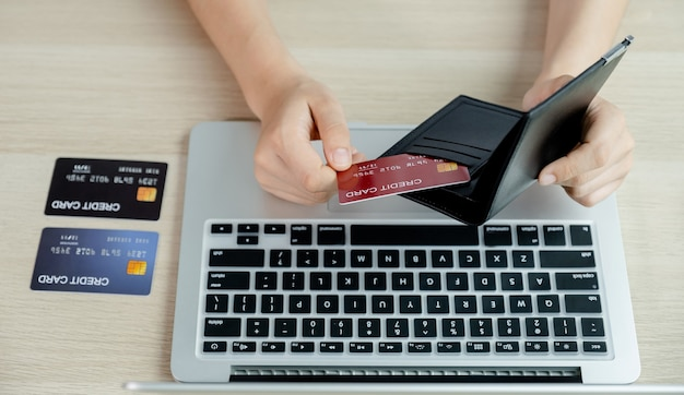 Ręka przedsiębiorców wyciąga karty kredytowe z kieszeni, aby robić zakupy online na laptopie z domu