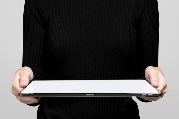 Ręka przedstawiająca niewidoczny hologram wyświetlający się z zaawansowanej technologii tabletu