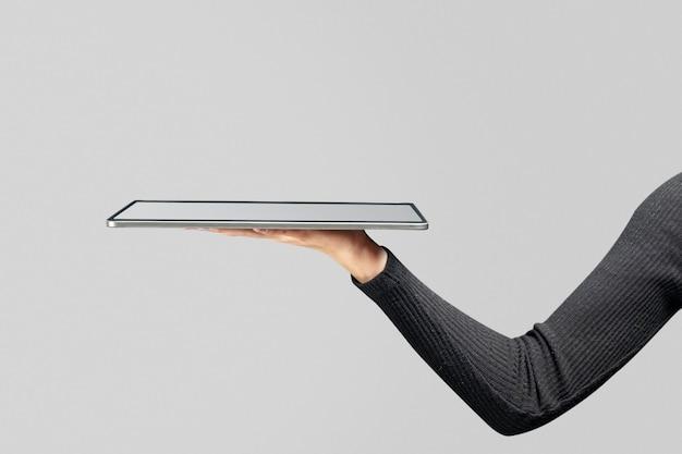 Ręka przedstawiająca niewidzialny hologram wyświetlający się z zaawansowanej technologii tabletu
