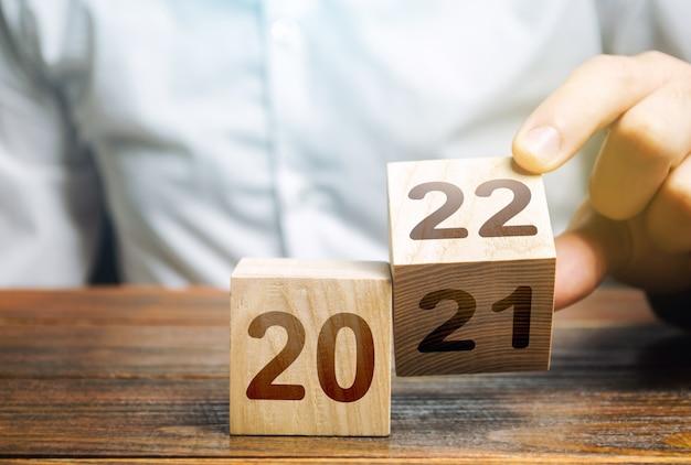 Ręka przerzuca klocek zmieniający się w 2021 na 2022 nowy rok rozpoczynający święta i święta bożego narodzenia